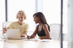 一起研究膝上型计算机的两名女实业家在会议室里 免版税库存图片