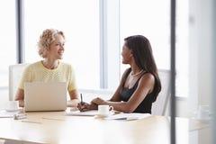 一起研究膝上型计算机的两名女实业家在会议室里 免版税库存照片