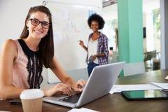 一起研究膝上型计算机的两名女实业家在办公室 库存照片
