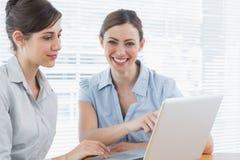 一起研究膝上型计算机的两名愉快的女实业家 免版税库存照片