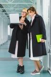 一起研究项目的两名典雅的女实业家在大厅 免版税库存图片