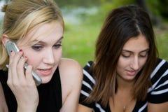一起移动电话的朋友(美丽的新金发碧眼的女人和Brune 免版税图库摄影