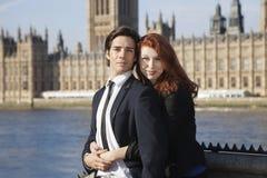 一起站立反对大本钟塔,伦敦,英国的年轻企业夫妇画象  免版税库存照片