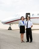 一起站立反对的空中小姐和飞行员 图库摄影