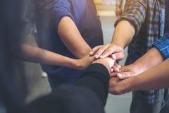 一起站立和加入他们的手的企业队办公室 免版税库存图片