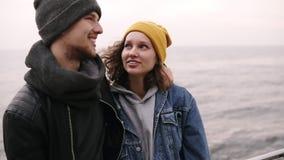 一起站立和拥抱在海边的行家年轻愉快的夫妇 穿衣服暖和,在寒冷的帽子的年轻人 股票视频