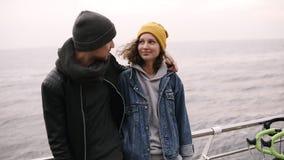 一起站立和拥抱在海边的行家年轻愉快的夫妇 穿衣服暖和,在寒冷的帽子的年轻人 股票录像