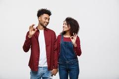 一起站立和显示好姿态的一对快乐的年轻非洲夫妇的画象被隔绝在白色背景 图库摄影