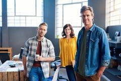 一起站立在一个现代办公室的被聚焦的年轻工友 库存图片