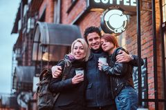 一起站立在容忍的愉快的朋友在咖啡馆附近外面 免版税图库摄影