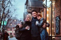 一起站立在容忍的愉快的朋友在咖啡馆附近外面 免版税库存图片