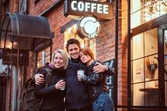 一起站立在容忍的愉快的朋友在咖啡馆附近外面 图库摄影