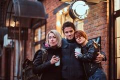 一起站立在容忍的朋友在咖啡馆附近外面 免版税图库摄影