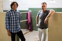 一起站立在槽枥的两个男性朋友 免版税库存照片
