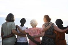 一起站立在海滩的不同的资深妇女背面图