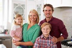 一起站立在现代厨房里的家庭画象 库存照片