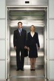 一起站立在电梯的企业同事 免版税图库摄影