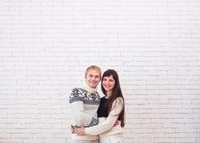 一起站立在白色砖背景的愉快的年轻夫妇 库存照片