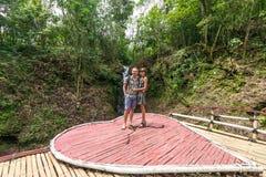 一起站立在站立在瀑布附近的爱的雨林夫妇的射击富感情的年轻蜜月夫妇  库存图片