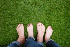 一起站立在草的夫妇混杂的腿 免版税库存照片