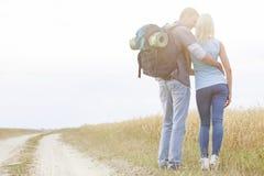 一起站立在领域的爱恋的远足的夫妇背面图  免版税库存照片