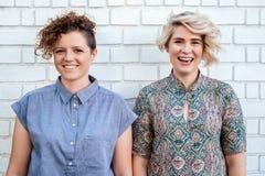 一起站立笑的年轻女同性恋的夫妇外面 免版税图库摄影