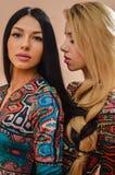 一起站立美丽的白肤金发和深色的性感的女孩 免版税库存图片
