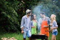 一起笑有的小组愉快的朋友室外烤肉 免版税库存图片