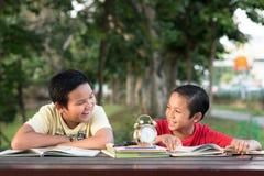 一起笑的亚裔男孩有乐趣时间在公园在晚上 图库摄影