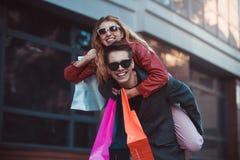 一起结合在购物 获得愉快的夫妇一起购物和乐趣 运载他的肩扛的男朋友女朋友 免版税库存图片