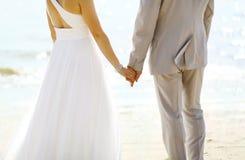 一起美丽的婚礼夫妇、新娘和新郎在海附近 免版税库存图片