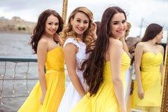 一起美丽的新娘和两个女傧相在夏天大阳台海餐馆 免版税库存图片