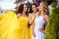 一起美丽的新娘和两个女傧相在夏天大阳台海餐馆 图库摄影