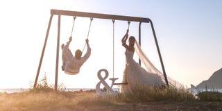 一起美好的夫妇在日落的摇摆 免版税库存照片