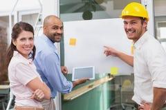 一起群策群力使用片剂的微笑的建筑师队 免版税库存照片