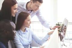 一起群策群力,当工作在计算机时的同事队  免版税库存照片