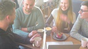一起聊天和笑在一间小咖啡馆或酒吧的愉快的小组朋友或企业同事 股票录像