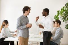 一起聊天在办公室duri的友好的多种族同事 免版税库存图片