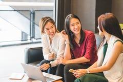 一起聊天在沙发的三个亚裔女孩在咖啡馆或咖啡店 闲话谈话,与小配件技术概念的偶然生活方式 库存图片