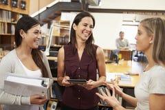 一起聊天在现代办公室的三位女性建筑师 免版税库存照片