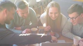 一起聊天,笑和使用计算机的愉快的小组朋友或企业同事在一间小咖啡馆或酒吧 股票视频