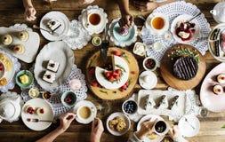 一起聚集在茶会吃蛋糕享受h的朋友 库存照片