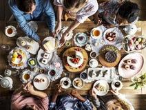 一起聚集在茶会吃蛋糕享受h的朋友 免版税库存图片