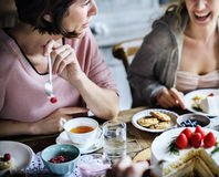 一起聚集在茶会吃蛋糕享受h的朋友 库存图片
