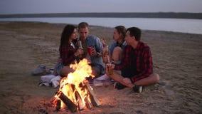 一起花费时间和喝啤酒的无忧无虑的年轻朋友由bonefire在海滩作为太阳开始设置 股票视频