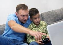 一起花费时间和打计算机游戏的父亲和儿子 免版税库存图片