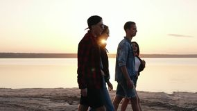 一起花费时间的年轻,好朋友侧视图  走在晚上黄昏的海滩 在约会的两对夫妇 股票视频