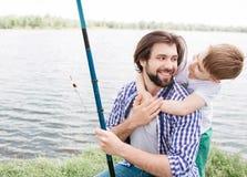 一起花费时间的有胡子的爸爸和他的小儿子的逗人喜爱的图片 当人微笑着和时,男孩拥抱他的爸爸 免版税库存图片