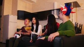 一起花费时间的朋友 坐沙发,观看的橄榄球和欢呼为队的四年轻人 股票录像