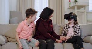 一起花费美好时光的两个孩子和他们的老婆婆在沙发上使用虚拟现实玻璃的一个逗人喜爱的女孩使 影视素材